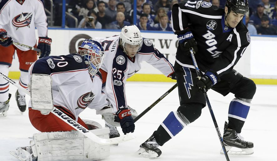 Tampa Bay Lightning center Brian Boyle (11) takes a pass in front of Columbus Blue Jackets goaltender Joonas Korpisalo (70), of Finland, and center William Karlsson (25), of Sweden, during the second period of an NHL hockey game Friday, Jan. 13, 2017, in Tampa, Fla. (AP Photo/Chris O'Meara)