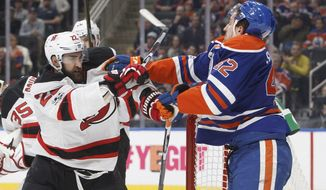 New Jersey Devils' Kyle Quincey (22) and Edmonton Oilers' Anton Slepyshev (42) mix it up during the second period of an NHL hockey game, Thursday, Jan. 12, 2017 in Edmonton, Alberta. (Jason Franson/The Canadian Press via AP)