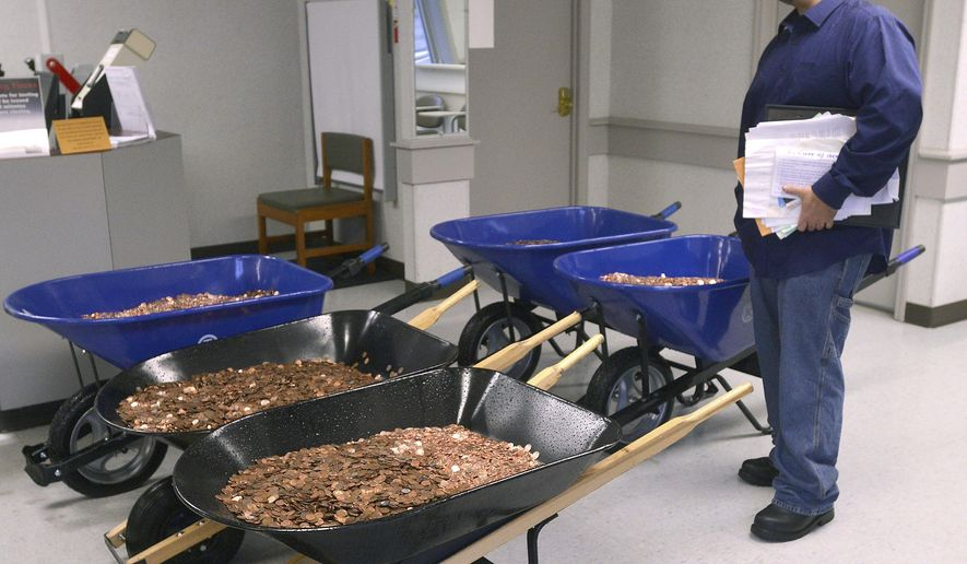 Nick Stafford waits for his number to be called Wednesday, Jan. 11, 2017, as he stands beside of 5 wheelbarrows full of change, mostly pennies, at the DMV in Lebanon, Va. Stafford was paying the sales tax on two cars that he was titling. Stafford had paid $165 to file three lawsuits in Russell County General District Court: two against specific employees at the Lebanon DMV and one against the DMV itself., which means he spent $1,005 to get 10 phone numbers and the satisfaction of delivering 300,000 pennies. Not to mention the nearly $3,000 he paid the DMV for the cars. (David Criggeru/The Bristol Herald-Courier via AP)