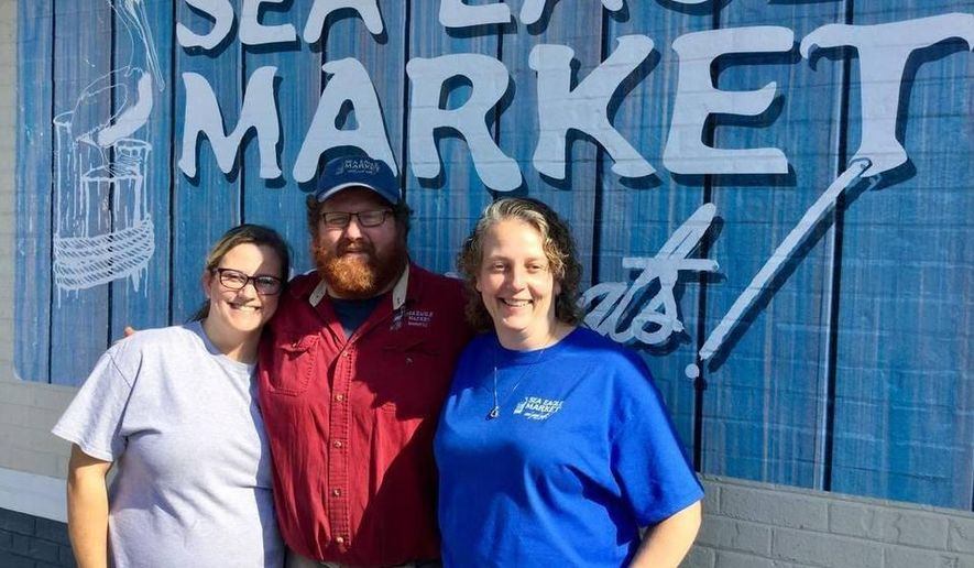 ADVANCE FOR USE SUNDAY, JAN. 15 - In this recent photo, Craig Reaves, center, poses with, from left, his daughter, Melena Argetsinger, and wife, Jana Reaves, pose at Sea Eagle Market, a family business that opened in a new location on Boundary Street in Beaufort, SC. He helped save a sheriff's office deputy during a fight in the parking lot in December. (Josh Mitelman/The Island Packet via AP)