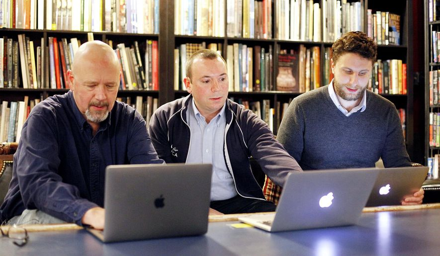 ADVANCE FOR USE SUNDAY, JAN. 15 - In this Dec. 20, 2016 photo, from left, Code for Asheville co-captain Eric Jackson, core team member Patrick Conant and co-captain Jesse Michel meet at Battery Park Book Exchange & Champagne Bar in Asheville, N.C. From homelessness to race and policing, Code for Asheville has embarked on a path to help the most vulnerable in the past year, following a national Code for America trend and pursuing a mission to use technology to make the community better. (Angela Wilhelm/The Asheville Citizen-Times via AP)