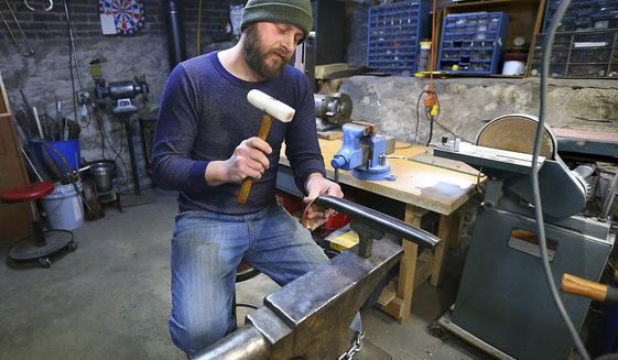 In this Jan. 9, 2017 photo, Adam Oldre works a piece of metal in his shop, in La Crosse, Wis. Oldre creates vessels and jewelry from recycled and repurposed metals. Oldre has been invited to participate in the American Concern for Artistry and Craftsmanship's ACAC Annual Craft and Fine Art Festival in New York, a prestigious juried show.  (Erik Daily  /La Crosse Tribune via AP)