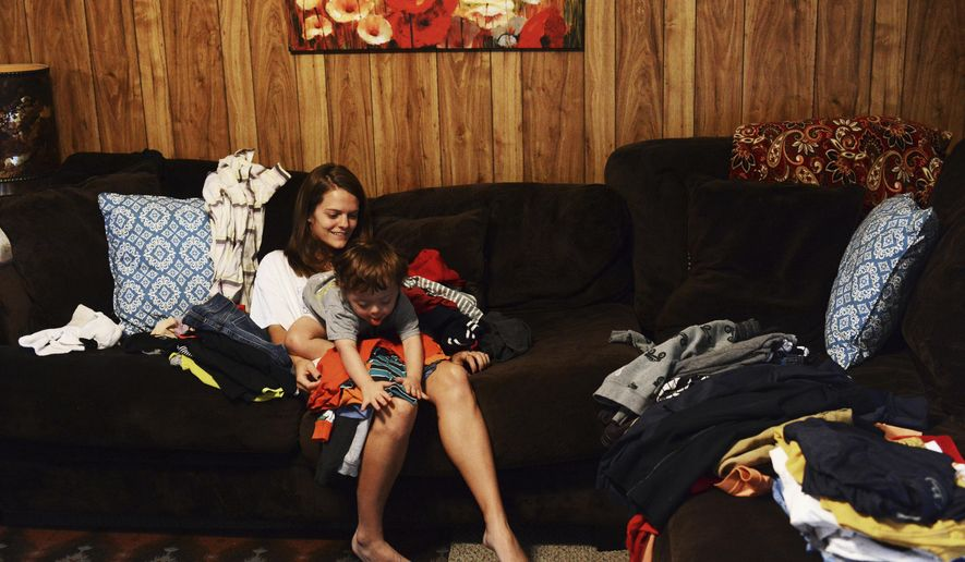 ADVANCE FOR MONDAY, JAN 16 AND THEREAFTER - In a Monday, Nov. 7, 2016 photo, Hallie Perkins takes a break from folding laundry as her 2-year-old son Ryker Cole plays on her lap at their home in West Monroe, La. Perkins' relationship with her son, who has Down syndrome, is filled with playfulness. They bond through play, and she talks to him constantly. She said she can tell he understands her, even though he does not talk back yet.  (Hannah Baldwin/Monroe News Star via AP)
