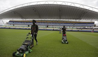 Workers level the grass at the Stade de l'Amitie, ahead of the opening ceremony and group A soccer matches between Gabon and Guinea Bissau at the Africa Nations Cup in Libreville, Gabon, Friday, Jan. 13, 2017. (AP Photo/Sunday Alamba)