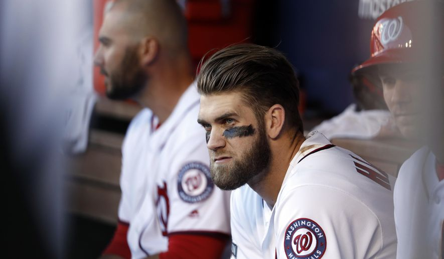 In this photo taken Oct. 9, 2016, Washington Nationals right fielder Bryce Harper (34) sits in the dugout during Game 2 of baseball's National League Division Series against the Los Angeles Dodgers, at Nationals Park in Washington. Harper and the Washington Nationals have agreed to a $13,625,000 contract for 2017, avoiding arbitration. The sides reached a deal Friday, Jan. 13, 2017, the deadline for players and teams to exchange arbitration figures ahead of hearings.(AP Photo/Alex Brandon)