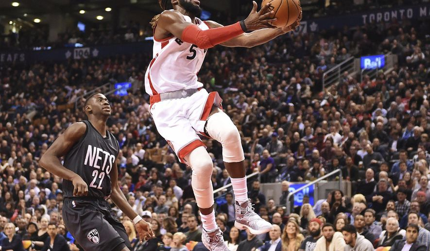 Toronto Raptors forward DeMarre Carroll drives past Brooklyn Nets guard Caris LeVert during the second half of an NBA basketball game Friday, Jan. 13, 2017, in Toronto. (Frank Gunn/The Canadian Press via AP)