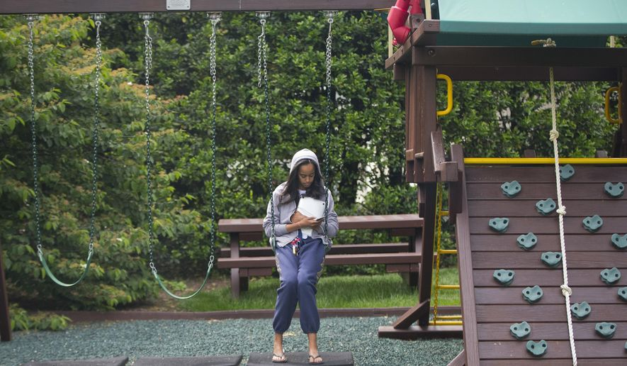 FILE - In this May 18, 2016 file photo, Malia Obama uses her phone at the swing and play set on the south grounds of the White House outside of the Oval Office in Washington. The swing set that President Barack Obama installed on the South Lawn for his young daughters eight years ago has a new home. The White House says the Obamas donated the set to a shelter in southeast Washington. The Obamas are planning to visit the Jobs Have Priority Naylor Road Program and join residents for a service project Monday in honor of Martin Luther King Jr. Day.  (AP Photo/Pablo Martinez Monsivais, File)