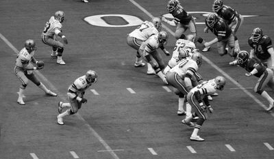 FILE - In this undated file photo, Dallas Cowboys quarterback takes the snap from a shotgun formation against the Atlanta Falcons during an NFL game. The Pro Football Hall of Fame _ which counts both Staubach and Cowboys coach Tom Landry among its members _ says San Francisco 49ers coach Red Hickey introduced a form of the shotgun offense to the sport in 1960, before abandoning it during the following season. But Landry's Cowboys get credit for bringing it back and popularizing it by positioning Staubach 5 yards behind the center. (AP Photo/File)