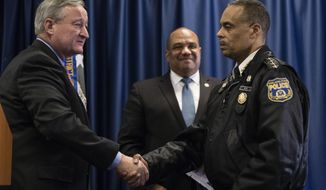 Department of Justice's Ronald Davis, director of the Office of Community Oriented Policing Services (COPS), center, looks on as Philadelphia Mayor Jim Kenney, left, and Philadelphia Police Commissioner Richard Ross Jr. shake hands during a news conference in Philadelphia, Friday, Jan. 13, 2017. The Justice Department reported on the latest progress by the Philadelphia Police Department in its reform efforts prompted by concerns over its use of deadly force. (AP Photo/Matt Rourke)