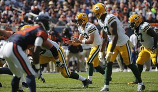 FILE - In this Sept. 13, 2015, file photo, Green Bay Packers quarterback Aaron Rodgers (12) takes a snap from a shotgun formation during the second half of an NFL football game against the Chicago Bears, in Chicago. Might be hard to believe while watching Aaron Rodgers, Russell Wilson or Ben Roethlisberger in the playoffs this weekend, but it wasn't all that long ago that the shotgun formation was something of a curiosity in the NFL, used less than once every five plays in 2006. (AP Photo/Charles Rex Arbogast, File)