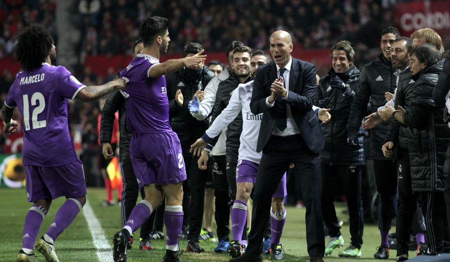 Real Madrid's Marco Asensio, second left, celebrates with teammates and Real Madrid's coach Zidane during a Spain's King's Cup soccer match between Real Madrid and Sevilla at the Ramon Sanchez Pizjuan stadium, in Seville, Spain on Thursday, Jan. 12, 2017. (AP Photo/Angel Fernandez)