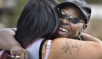 Velma Aiken, the paternal grandmother of Kamiyah Mobley, who was kidnapped as an infant 18 years ago, gets a congratulatory hug from a family member after Mobley was found safe Friday, Jan. 13, 2017, in Jacksonville, Fla.  (Will Dickey /The Florida Times-Union via AP)
