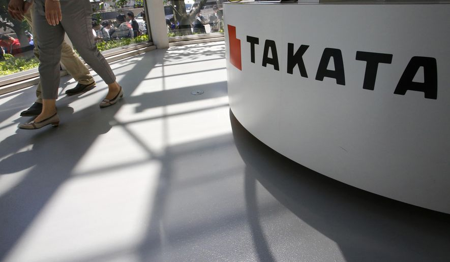 FILE - In this May 4, 2016, file photo, visitors walk by a Takata Corp. desk at an automaker's showroom in Tokyo.  The Justice Department is planning to announce a criminal penalty against the Japanese air bag maker  as part of its investigation into the company's defective air bag inflators. The department has scheduled a news conference Friday, Jan. 13, 2017 in Detroit to make the announcement. (AP Photo/Shizuo Kambayashi, File)