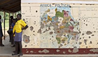 FILE - In this Nov. 15, 2016 file photo, students line up outside a classroom with a map of Africa on its wall, in Yei, in southern South Sudan. The Obama administration is set to ease sanctions against Sudan and broaden now limited talks with the long estranged African government, a U.S.-designated terrorism sponsor whose leader has been indicted on war crimes charges, The Associated Press learned Thursday, Jan. 12, 2017. (AP Photo/Justin Lynch, File)