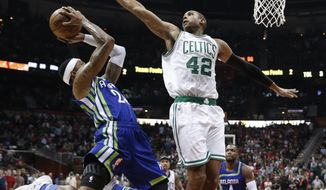 Atlanta Hawks forward Kent Bazemore (24) goes in for a shot as Boston Celtics center Al Horford (42) defends during the second half of an NBA basketball game Friday, Jan. 13, 2017, in Atlanta. Boston won 103-101. (AP Photo/John Bazemore)