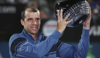 Gilles Muller of Luxembourg holds his trophy as he celebrates his win over Britain's Daniel Evans in the men's singles final of the Sydney International tennis tournament in Sydney, Australia, Saturday, Jan. 14, 2017. (AP Photo/Rick Rycroft)