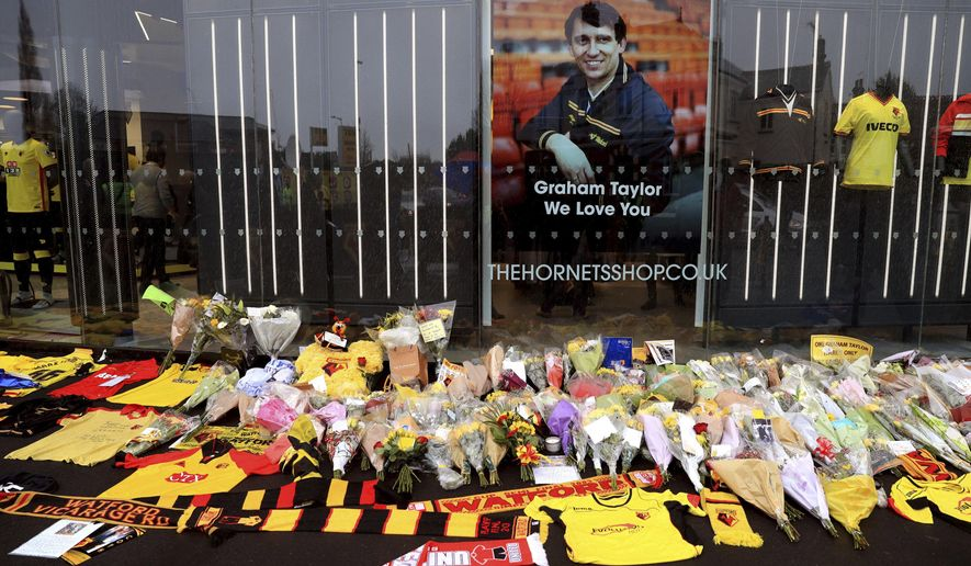 Tributes are laid out in memory of former Watford and England manager Graham Taylor ahead of their Premier League match against Middlebrough at Vicarage Road, Watford, England, Saturday, Jan. 14, 2017. Taylor died on Thursday at the age of 72. (Adam Davy/PA via AP)