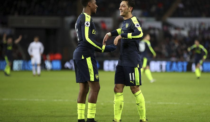 Arsenal's Alex Iwobi, right, celebrates after his shot deflected off Swansea City's Kyle Naughton (not pictured) for a own goal and Arsenal's third of the game during the English Premier League soccer match between Swansea City and Arsenal at the Liberty Stadium, Swansea, Wales, Saturday, Jan. 14, 2017.(Nick Potts/PA via AP)