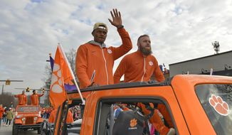 Clemson's Deshaun Watson, left, and Ben Boulware wave to the crowd during a parade honoring the NCAA college football champions, Saturday, Jan. 14, 2017, in Clemson, S.C. Clemson won the title with a 35-31 victory over defending national champ Alabama last Monday night. (AP Photo/Richard Shiro)