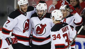New Jersey Devils' Kyle Palmieri, center, celebrates his goal with teammates during the first period of an NHL hockey game against the Calgary Flames, Friday, Jan. 13. 2017, in Calgary, Alberta. (Jeff McIntosh/The Canadian Press via AP)