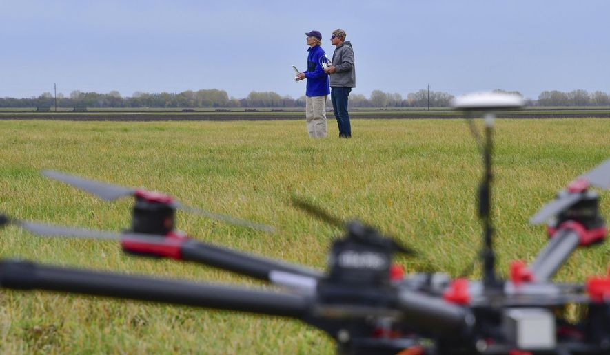 In this Oct. 17, 2016 photo, Gary Niemeier, left, practices flying a drone alongside Eric Goetsch, a senior instructor pilot for SkySkopes in Grand Forks, N.D.  Niemeier was the test pilot for the flight certification of SkySkopes Academy, a new course for drone enthusiasts that targets students between 8th and 12th grades.  With the number of commercial drone operations outpacing the pool of certified drone pilots, experts say more training is needed to help young flyers operate the planes legally and safely.  (Brandi Jewett/SkySKopes Academy via AP)