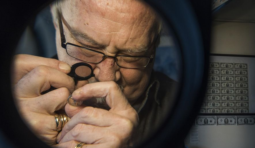 "ADVANCE FOR WEEKEND EDITIONS - In this Thursday, Jan. 5, 2017, photo, Rich Borland, 72, of Lower Burrell, Pa., examines a Roman republic ""Head of Roma"" coin from 128 B.C. at his shop in Lower Burrell. Borland took over The Coin Store from a friend in January 1998 but has been collecting coins since he was 12. (Andrew Russell/Pittsburgh Tribune-Review via AP)"