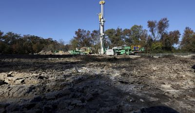 In a Nov, 17, 2016 photo, a drilling rig operated by the U.S. Geological Survey drills down to bedrock to install a land subsidence-measuring instrument called an extensometer in northern Suffolk, WVa..  (Steve Earley/The Virginian-Pilot via AP)