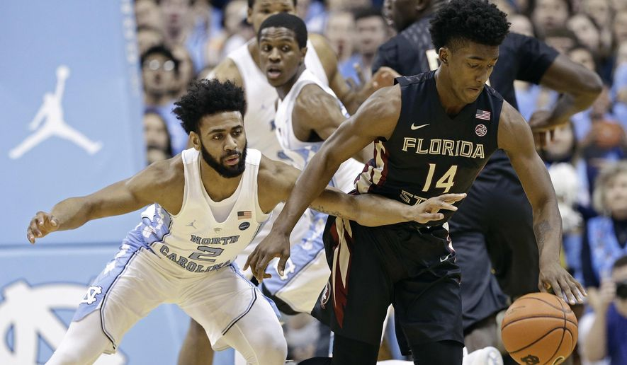 North Carolina's Joel Berry II (2) reaches in against Florida State's Terance Mann (14) during the first half of an NCAA college basketball game in Chapel Hill, N.C., Saturday, Jan. 14, 2017. (AP Photo/Gerry Broome)