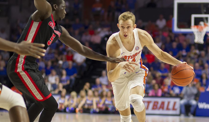 Florida guard Canyon Barry (24) dribbles past Georgia forward Pape Diatta (5) during the first half of an NCAA college basketball game in Gainesville, Fla., Saturday, Jan. 14, 2017. (AP Photo/Ron Irby)