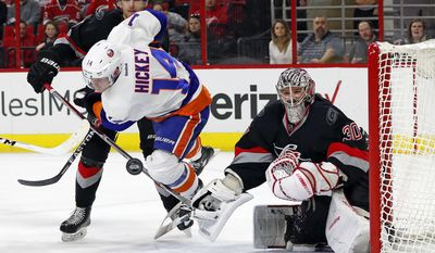 New York Islanders' Thomas Hickey (14) dives between Carolina Hurricanes' Noah Hanifin (5) and goalie Cam Ward (30) as he chases the puck during the first period of an NHL hockey game, Saturday, Jan. 14, 2017, in Raleigh, N.C. (AP Photo/Karl B DeBlaker)