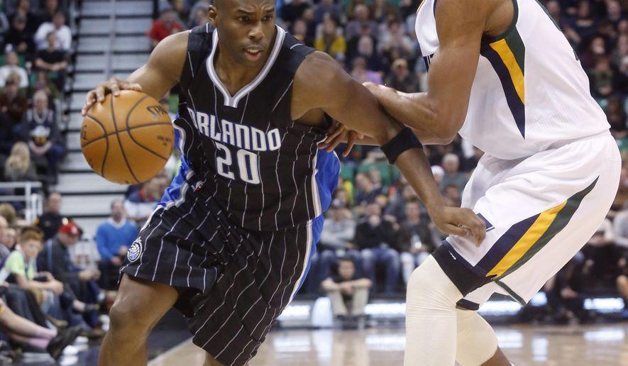 Orlando Magic's Jodie Meeks (20) dribbles past Utah Jazz's Rodney Hood during the first half of an NBA basketball game Saturday, Jan. 14, 2017, in Salt Lake City. (AP Photo/Kim Raff)