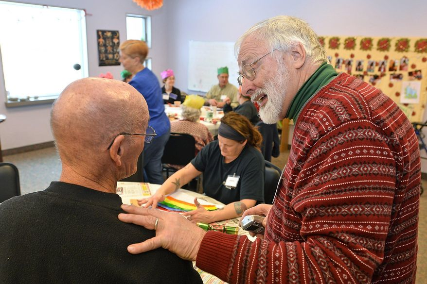 In this Jan. 8, 2017 photo, Wilmer Laird, left, of Union City, is greeted by Tom Schlaudecker at the Memory Cafe, which is held weekly at the Unitarian Universalist Congregation of Erie in Millcreek Township, Pa. About two years ago, Schlaudecker started the group, which is free and features music, art, readings and social activities for older people with dementia, and their caregivers. (Christopher Millette /Erie Times-News via AP)