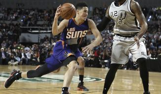 Phoenix Suns Devin Booker, left, drives the ball as San Antonio Spurs LaMarcus Aldridge attempts to block him, in the first half of their regular-season NBA basketball game in Mexico City, Saturday, Jan. 14, 2017. (AP Photo/Rebecca Blackwell)