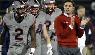 FILE - Int his Nov. 4, 2016, file photo, Connecticut coach Bob Diaco watches his players warm up for an NCAA college football game against Temple in East Hartford, Conn. Former UConn head coach Bob Diaco has been named the new defensive coordinator at Nebraska.  UConn fired Diaco last month after three straight losing seasons. Nebraska coach Mike Riley hired Diaco to take over a Nebraska defense that struggled in the most important games. He replaces Mark Banker, who was fired Wednesday.  (AP Photo/Elise Amendola, File_