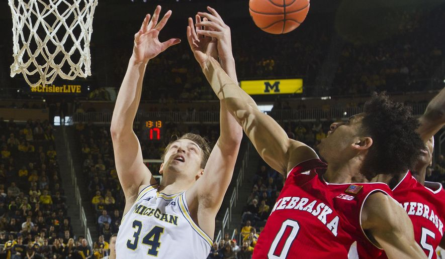 Michigan forward Mark Donnal (34) contest for a rebound with Nebraska guard Tai Webster (0), of New Zealand, in the first half of an NCAA college basketball game at Crisler Center in Ann Arbor, Mich., Saturday, Jan. 14, 2017. (AP Photo/Tony Ding)