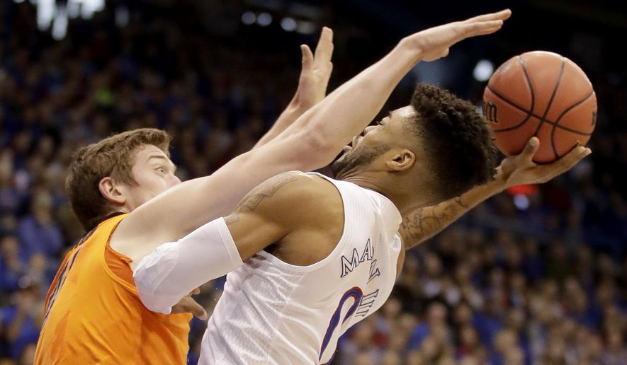 Kansas' Frank Mason III (0) is pressured by Oklahoma State's Mitchell Solomon as he shoots during the first half of an NCAA college basketball game, Saturday, Jan. 14, 2017, in Lawrence, Kan. (AP Photo/Charlie Riedel)