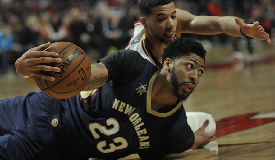 New Orleans Pelicans' Anthony Davis (23) looks to pass after battling Chicago Bulls' Michael Carter-Williams (7) for the ball during the first half of an NBA basketball game Saturday, Jan. 14, 2017, in Chicago. (AP Photo/Paul Beaty)