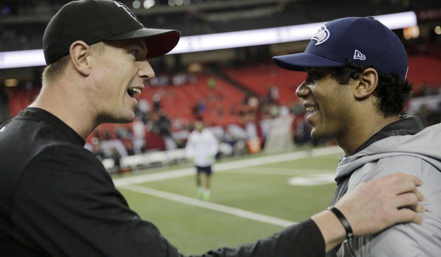 Atlanta Falcons quarterback Matt Ryan, left, speaks with Seattle Seahawks quarterback Russell Wilson before the first half of an NFL football NFC divisional playoff game, Saturday, Jan. 14, 2017, in Atlanta. (AP Photo/David Goldman)