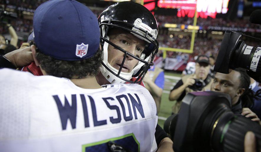 Atlanta Falcons quarterback Matt Ryan, right, embraces Seattle Seahawks quarterback Russell Wilson after an NFL football divisional football game, Saturday, Jan. 14, 2017, in Atlanta. The Falcons won 36-20. (AP Photo/David Goldman)