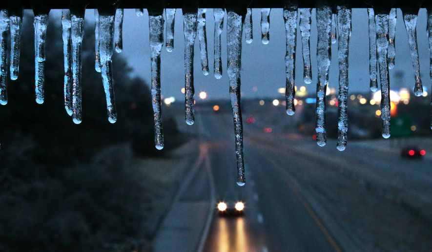 Traffic is sparse on Interstate 55 as ice hangs from the Main Street bridge on Friday, Jan. 13, 2017 in Festus, Mo.  A thick glaze of ice covered roads from Oklahoma to southern Illinois on Friday amid a winter storm that caused numerous wrecks, forced school cancellations, grounded flights and prompted dire warnings for people to stay home.(Robert Cohen/St. Louis Post-Dispatch via AP)