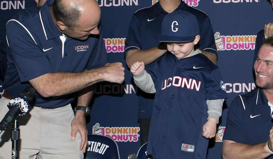 In this April 20, 2015 photo released by the University of Connecticut, leukemia patient Grayson Hand, center, bumps fists with UConn baseball coach Jim Penders, left, at a ceremony where he signed an honorary national letter of intent to become part of the UConn baseball team in Storrs, Conn. Hand has formed a special bond with UConn pitcher Ryan Radue, who was diagnosed with cancer later in 2015. (Stephen Slade/UConn Athletics via AP)