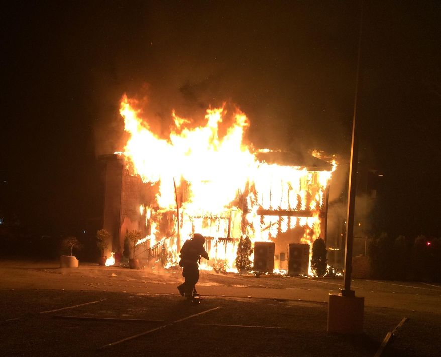 This photo provided by Bellevue, Wash., Fire Department, a fire burns at the Islamic Center of the Eastside in Bellevue, Wash., on Saturday, Jan. 14, 2017.  Police say a man is in custody after a suspicious fire severely damaged the mosque overnight.  Authorities say that as firefighters doused the flames, police found a 37-year-old man near the building and arrested him for investigation of arson. Police spokesman Seth Tyler says investigators believe the man is the sole suspect. His name was not immediately released. The mosque was unoccupied at the time and no injuries were reported. (Bellevue, Wash., Fire Department via AP)