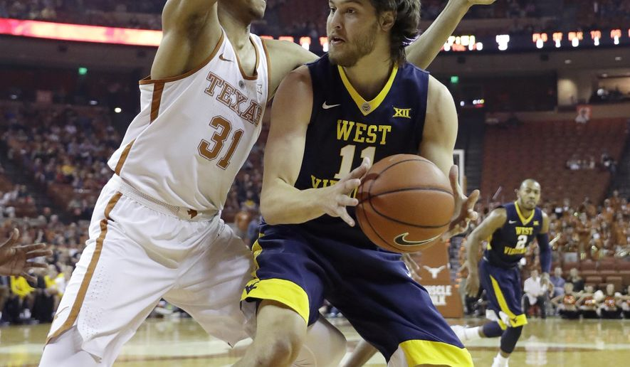 West Virginia forward Nathan Adrian (11) is pressured by Texas forward Jarrett Allen (31) during the first half of an NCAA college basketball game, Saturday, Jan. 14, 2017, in Austin, Texas. (AP Photo/Eric Gay)
