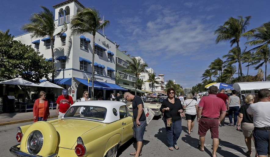 People look at vintage cars during Art Deco Weekend, on Ocean Drive, Sunday, Jan. 15, 2017, in Miami Beach, Fla. Art Deco Weekend was created nearly 40 years ago by the Miami Design Preservation League to showcase the beautiful Art Deco buildings of South Beach. (Patrick Farrell/Miami Herald via AP)