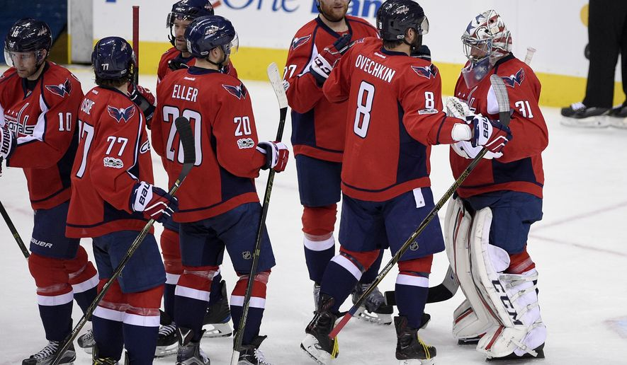 Washington Capitals goalie Philipp Grubauer (31), of Germany, Washington Capitals left wing Alex Ovechkin (8), of Russia, and others celebrate 5-0 win over the Philadelphia Flyers after an NHL hockey game, Sunday, Jan. 15, 2017, in Washington. The Capitals won 5-0. (AP Photo/Nick Wass)