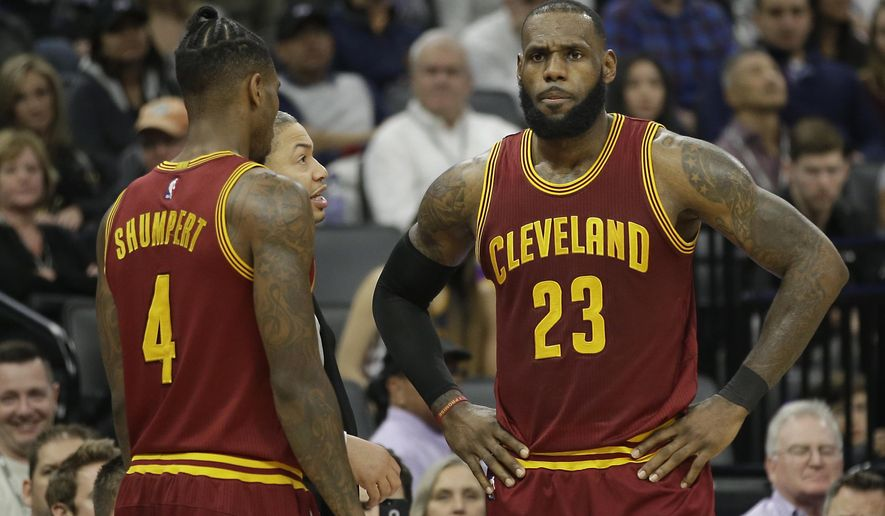 Cleveland Cavaliers head coach Tyronn Lue, center, talks with LeBron James, right, as Iman Shumpert, left, looks on during the second half of an NBA basketball game against the Sacramento Kings Friday, Jan. 13, 2017, in Sacramento, Calif. The Cavaliers won 120-108. (AP Photo/Rich Pedroncelli)