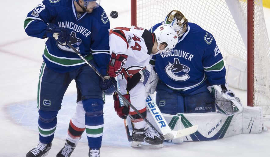 Vancouver Canucks defenceman Alexander Edler (23) looks on as New Jersey Devils left wing Miles Wood (44) tries to get a shot past Canucks goalie Jacob Markstrom (25) during the third period of an NHL hockey game in Vancouver, British Columbia, Sunday, Jan. 15, 2017. (Jonathan Hayward/The Canadian Press via AP)