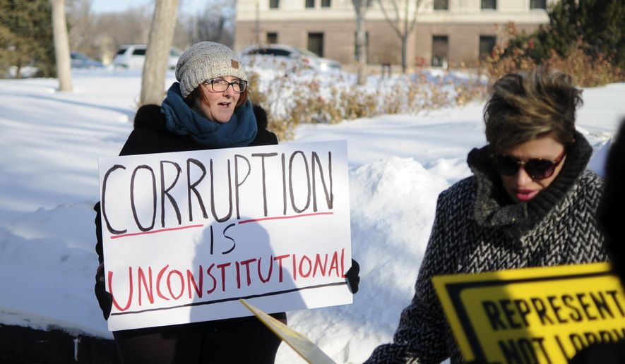 In this Tuesday, Jan. 10, 2017, photo, Pierre, S.D., resident Roxanne Weber rallies in support of a voter-approved government ethics overhaul in front of the state Capitol in Pierre. Republican Gov. Dennis Daugaard said in his State of the State address he will support efforts to repeal and replace the initiative. (AP Photo/James Nord)