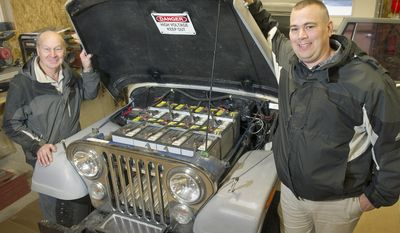ADVANCE FOR USE SUNDAY, JAN. 15 - In this Jan. 5, 2017 photo, Adam Verhage, right, and his father Carroll show the eight 12 volt batteries, which sit atop an electric motor mated to the vehicle's original drivetrain, in the electric-powered CJ-7 Jeep they built in Geneva, Neb.  (Eric Gregory/The Journal-Star via AP)