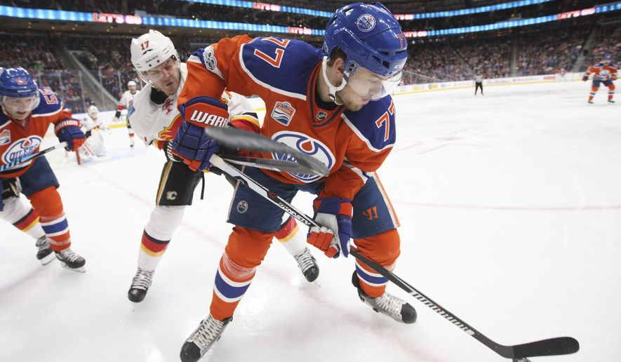 Calgary Flames' Lance Bouma (17) and Edmonton Oilers' Oscar Klefbom (77) vie for the puck during the second period of an NHL hockey game Saturday, Jan. 14, 2017, in Edmonton, Alberta. (Jason Franson/The Canadian Press via AP)